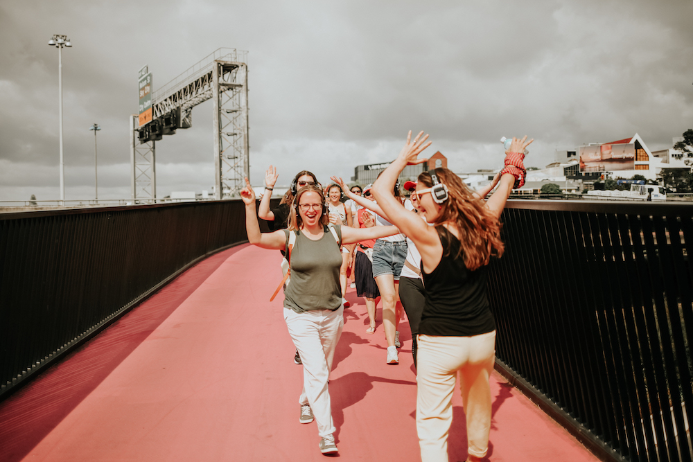 Friends rocking the Pink Path in Auckland wearing headphones